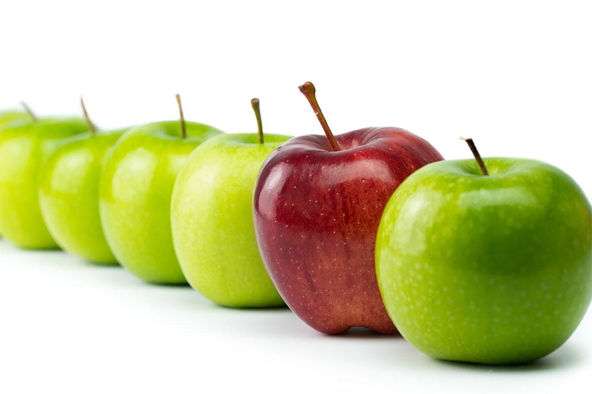 ein roter Apfel unter mehreren grünen